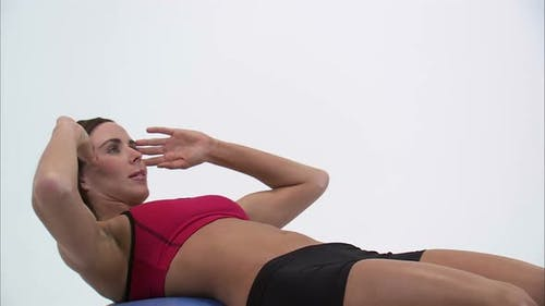Royalty Free Stock Footage of Woman doing sit-ups on an exercise ball.