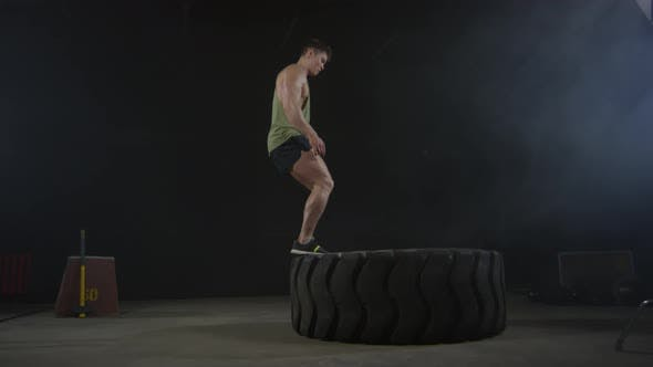 Thumbnail for Man Using Tractor Tire for Workout