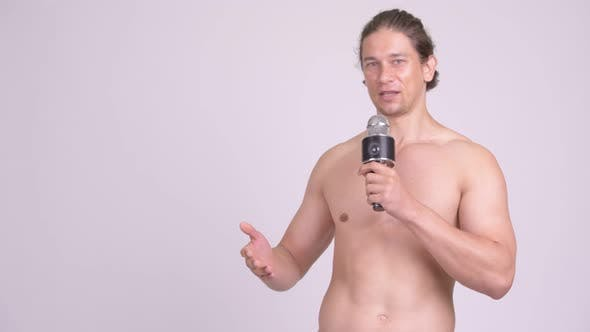 Thumbnail for Muscular Shirtless Man Presenting Something with Microphone
