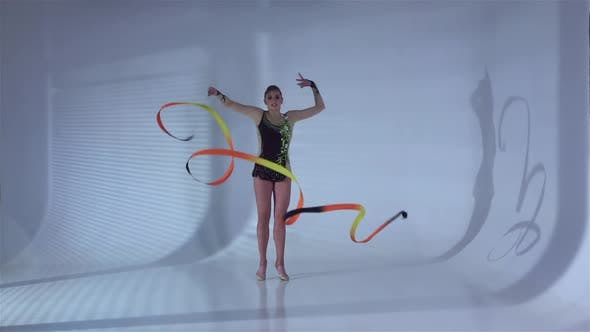 Thumbnail for Gymnast Circle Around Yourself with the Tape in the Hands. White Background. Slow Motion