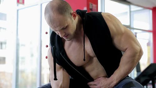 Muscular Male Athlete Training Hard in the Gym, Pumping Iron to Build Muscles
