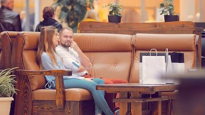 Couple Sitting in the Mall on the Couch