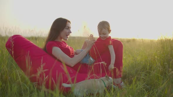 Thumbnail for Playful Mom Tickling Laughing Baby Girl Outdoors