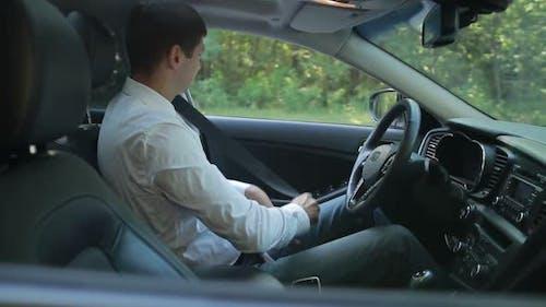 Businessman in Car Fastening Seatbelt
