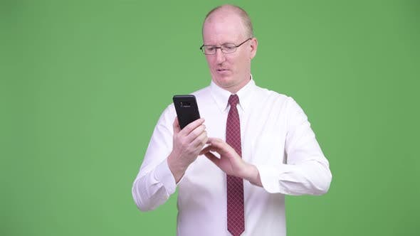 Cover Image for Stressed Mature Bald Businessman Using Phone and Getting Bad News