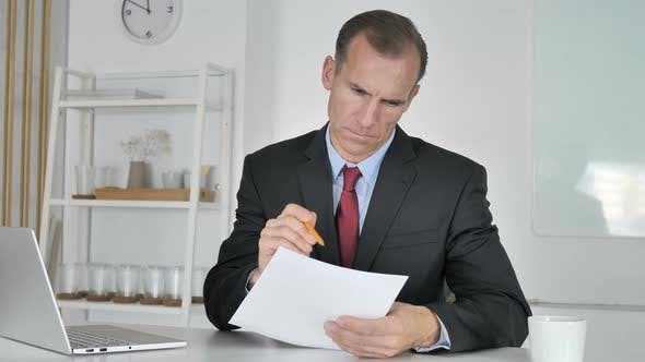 Thumbnail for Middle Aged Businessman Reading Documents in Office