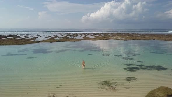 Thumbnail for Drohne fliegt von der Küste zu einem schönen schlanken Mädchen