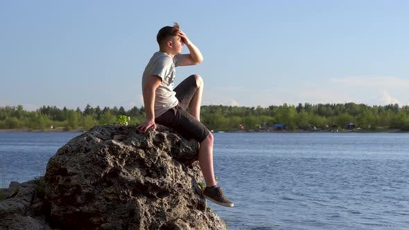 Thumbnail for A Young Man Sits on a Stone By the River and Admires Nature. A Man in Nature Closeup.