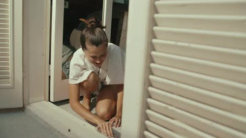 Young Woman Preparing to Paint the Wooden Door in House Sanding Doorstep
