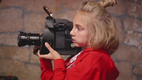 Young Girl Cinematographer Using Retro Camcorder for Shooting Video in Brick Studio, Teenager Girl