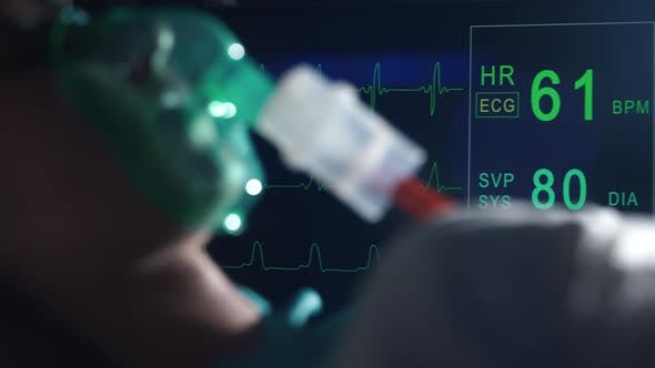 A Female Patient in Medical Mask is Breathing Oxygen Support in a Hospital Next to Heart Rate