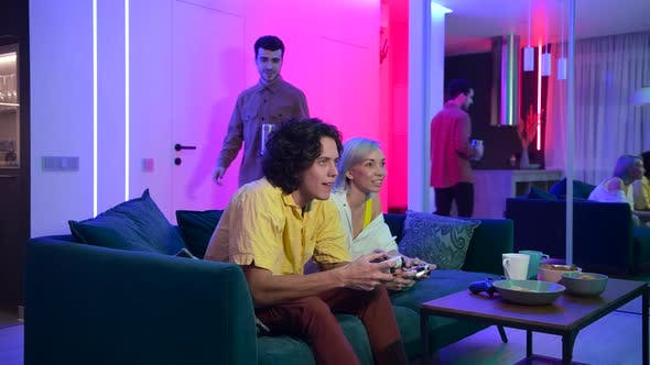 Thumbnail for Friend of a Young Couple Comes To Their Home To Play Games on Gaming Console on Pleasant Evening
