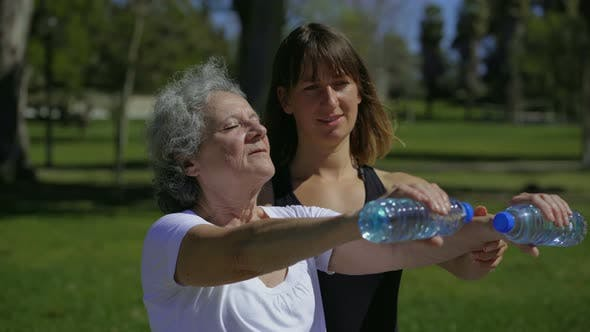 Thumbnail for Calm Senior Woman Training with Cheerful Personal Coach in Park