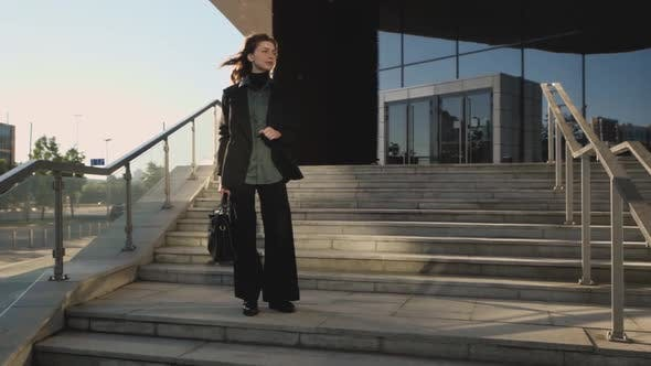 A Businesswoman Stands on the Stairs of a Large Corporation Looking Around