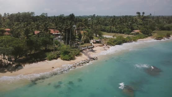 Thumbnail for Drone Flying Around Small Idyllic Ocean Resort House with Palm Trees, Waves Washing the Shore with