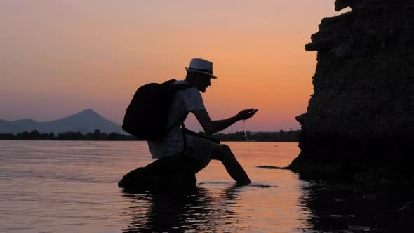 Thumbnail for Silhouette of a Man Sitting on the Stone with Seascape on Background