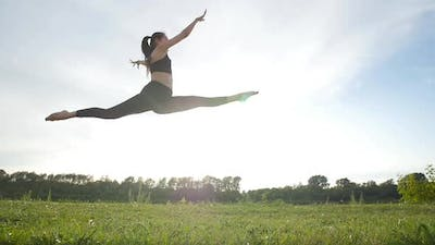 Sport and Healthy Lifestyle Concept. Young Athletic Woman in a Long Jump Sunny Sky Background