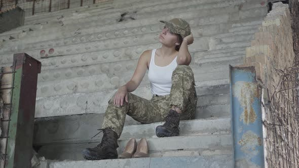 Thumbnail for Young Sad Woman in Military Uniform Sitting on the Cold Concrete Stairs in the Abandoned Building