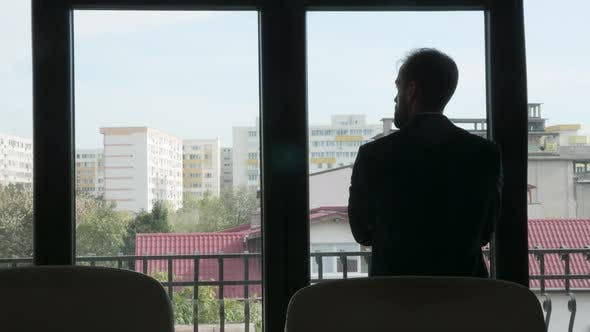 Thumbnail for Silhouette of Businessman Sitting Next To a Big Window
