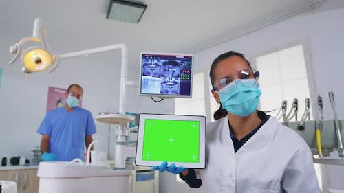 Patient Pov of Dentist Analisyng Xray Using Tablet with Green Screen