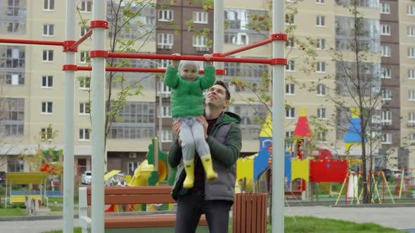 Thumbnail for Caucasian Dad Helping Young Son Do Pull-Ups at Playground