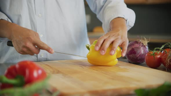Thumbnail for Close up shot of man cutting yellow bell pepper