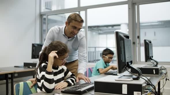 Focused Schoolgirl Overlooking Teacher Typing