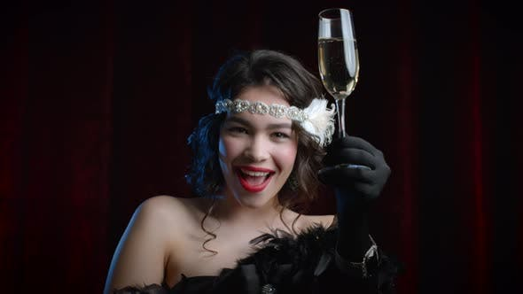 Thumbnail for Vintage Styled Woman Dressed in Gatsby Style Raises a Glass of Champagne