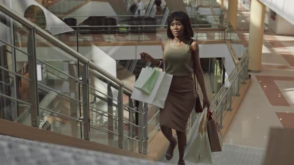 Thumbnail for Happy Woman Going Upstairs with Shopping Bags