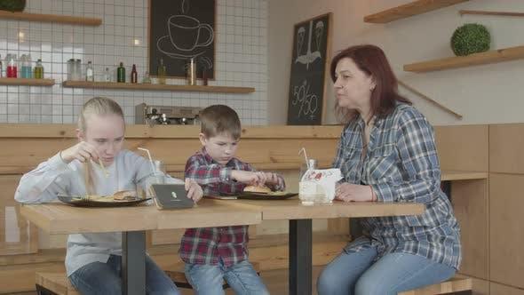 Babysitter Forbidding Kids Gaming Phones in Cafe