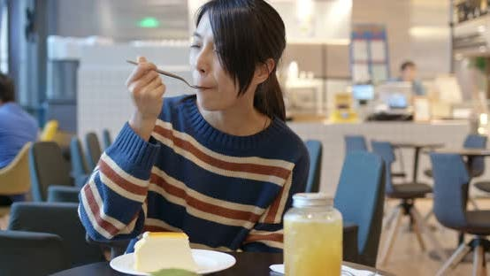 Thumbnail for Asian Woman enjoy the cake in coffee shop