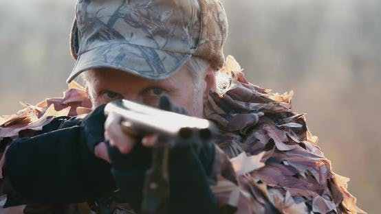 Thumbnail for Portrait of Hunter in Hunting Equipment Aims With the Rifle, Lies in Wait in the Field Sunset Light