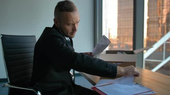 Thumbnail for Selbstbewusster Geschäftsmann im formellen Anzug mit Umzugskasten im Büro Auspacken von Artikeln