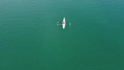 Two Female Driving Canoe on Sea