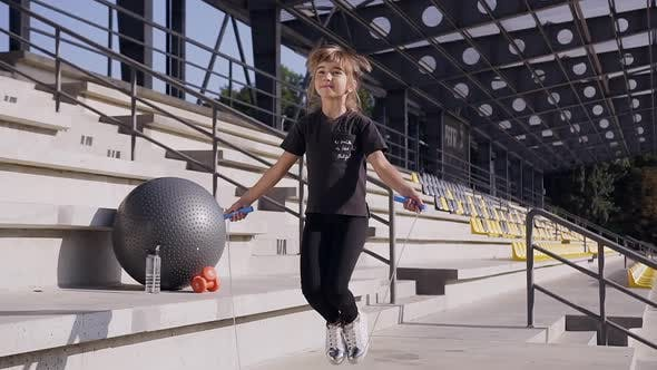 Thumbnail for Little Girl with Ponytail in Black t-shirt and Leggings Jumping with Skipping Rope
