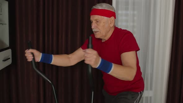 Senior Man in Sportswear Using Orbitrek in Living Room Doing Sport Training Cardio Exercises at Home