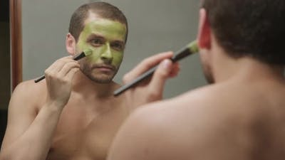 Attractive male using beauty cream product for skin health in Front of The Mirror