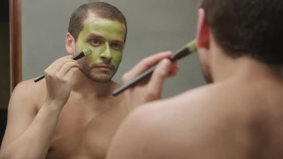 Thumbnail for Attractive male using beauty cream product for skin health in Front of The Mirror