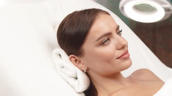 LOVELY WOMAN LYING AT SPA ON WHITE TOWEL