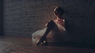 Young Beautiful Ballerina Sitting Tired in a Dark Room