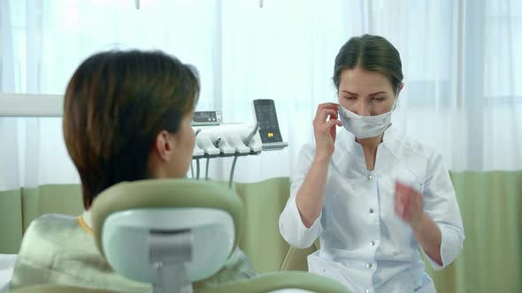 Thumbnail for Dentist Puts on a Mask While Talking with a Woman
