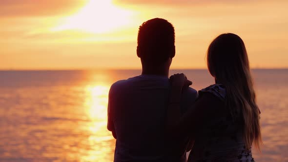 Cover Image for Multi-ethnic Couple in Love Admires the Sunset Over the Ocean