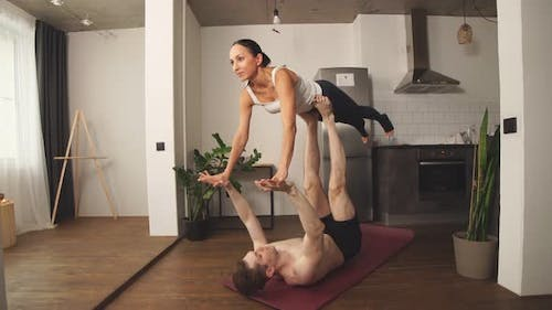 Loving Young Couple Having Acro Yoga Practice on the Floor at Home.