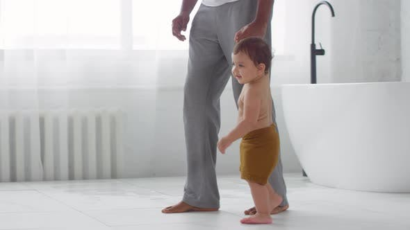 Father and Toddler Walking in Bathroom