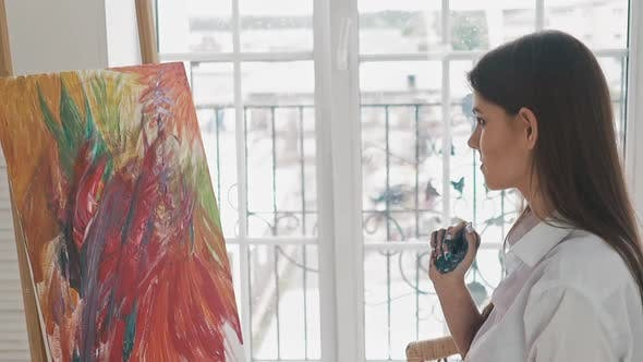 Woman Artist with Palm in Paint Looks at Abstract Painting