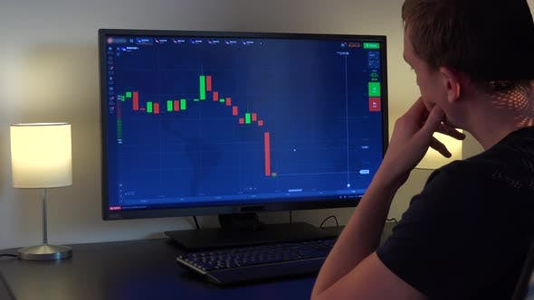 Thumbnail for A Man Sits at a Table and Looks at a Candle Chart on a Computer Screen, Then Gets and Up Walks Away