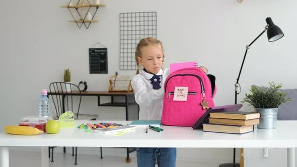 Pupil Girl Prepares Backpack with School Supplies