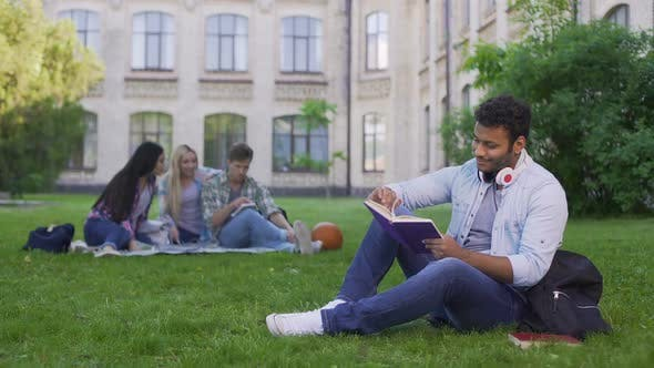 Thumbnail for Happy Biracial Male Student Sitting on Grass and Reading Interesting Book