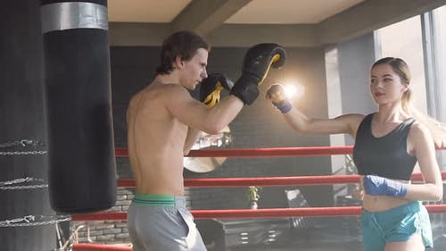 Young Female Boxer Training with Male Coach on Boxing Ring