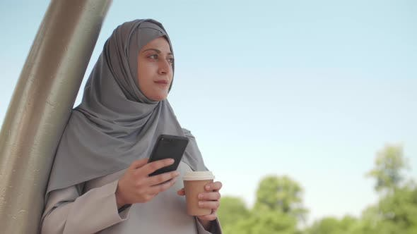 Thumbnail for Muslim Woman with Smartphone and Coffee Outdoors